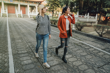 full length two travel best friends walking on road in chinese temple on background. women tourists looking aside sightseeing smiling hands touch straw hat playing with hair. relax female with sunset