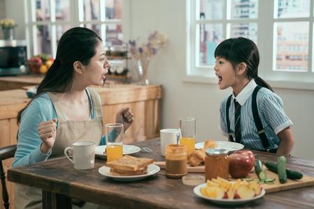 Schöne asiatische Hausfrau mit schlechter Tochter des kleinen Mädchens, die sich anschreit. Konzept des Familienkonflikts. wütende mutter und kind in uniform streiten morgens vor der schule in der frühstückszeit. Standard-Bild