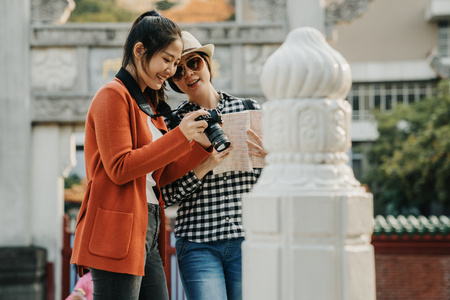 Group of Asian women standing close looking check photo in camera while traveling at chinese style park in beijing temple. Lifestyle friends tourist holiday. female on bridge by white stone railing