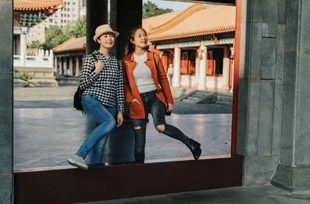 full length asian travel women cross threshold of chinese confucius temple in beijing china. curious smiling girls friends walking standing in exit sightseeing beautiful view enjoy sunset moment Stock Photo