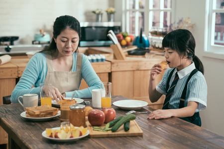 sleepy tired asian little girl falling asleep at breakfast time while eating croissant. chinese parent and kid family time in morning. daughter taking having bread bun taking nap at kitchen table. Reklamní fotografie