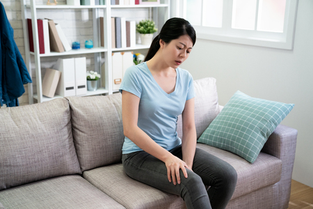Closeup young woman sitting on sofa and feeling knee pain and massage her knee at home. Healthcare and medical concept. asian girl housewife sitting on couch frowning looking at hurting legs