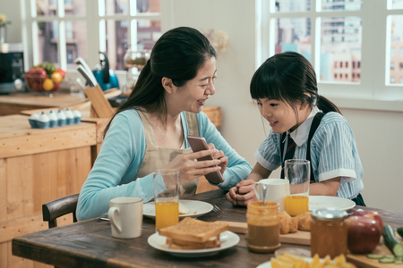 Funny mom and lovely child are having fun with phone. young asian housewife in apron and cute daughter in uniform sitting at morning kitchen table with tasty healthy meal breakfast. kid interested. Foto de archivo