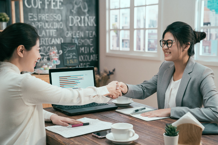 portrait of asian woman business people shaking hands finishing up meeting coffee shop. mortgage insurance broker financial advisor agent smiling to customer in cafe. two ladies make deal agreement