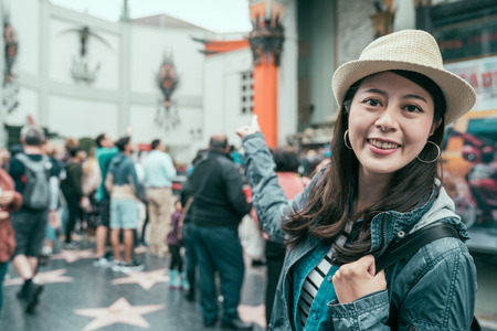 young smiling asian traveler woman in straw hat finger point showing background of famous chinese theatre on hollywood walk of fame. beautiful happy backpacker girl in spring holidays travel usa.