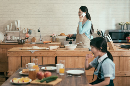 ignore family gadget addiction. busy asian wife mother holding wooden plate with croissant walking in modern kitchen talking with husband on cellphone in morning. little girl eating having breakfast