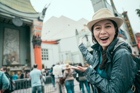 excited female tourist open mouth laughing and face camera at theatre hollywood street.