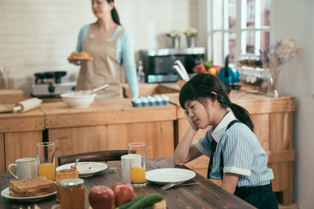 Tired asian chinese little girl in uniform fell asleep in early morning while waiting for breakfas. elegant wife mom in apron busy prepare handmade delicious healthy meal