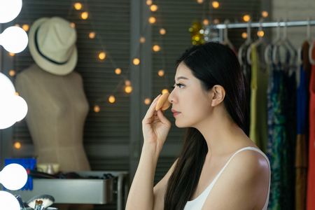 side view of asian lady looking herself while puff the powder on cheek in dressing room. Stock Photo