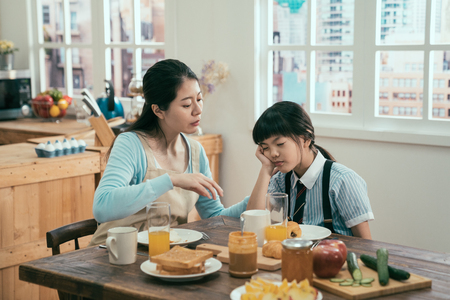 young beautiful asian korean mother wakes up sleeping daughter in the morning at kitchen.
