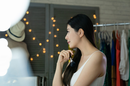 Side view of beautiful young korean woman performer looking at reflection in mirror in backstage room. Stock Photo