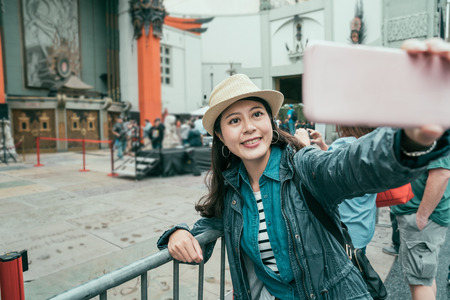 vintage style of young beautiful asian woman smile making self portrait with cell phone. Stock Photo