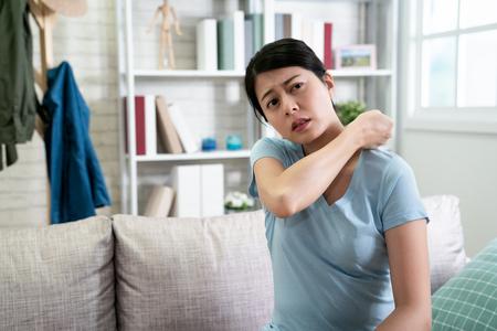 asiatische junge frau mit schulterschmerzen, die auf der couch sitzt und ihre körpermassage fallen lässt, um schmerzhaft zu lösen. Standard-Bild
