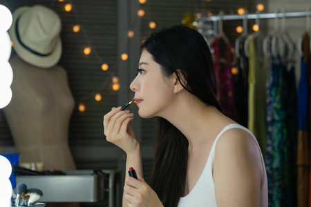 Young woman korean actress applying lipstick at makeup table in dressing room.