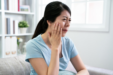 beautiful elegant asian woman has toothache sitting on couch with hurting uncomfortable face frowning. young chinese housewife at home having teeth painful problem. unhealthy concept illness female. Archivio Fotografico