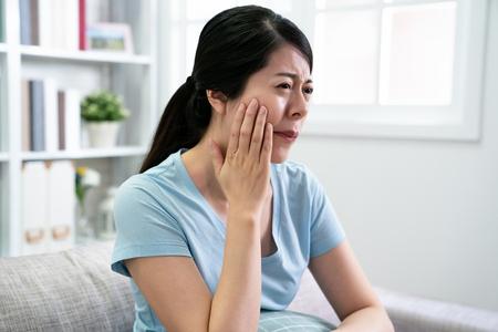 schöne elegante asiatische frau hat zahnschmerzen, die auf der couch sitzen und verletzendes unbequemes gesicht runzelt junge chinesische hausfrau zu hause mit zahnschmerzen. ungesunde Konzeptkrankheit weiblich.