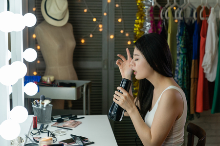 Young pretty chinese woman singer singing with hair dryer instead microphone in dressing room sitting at vanity table. nervous asian girl practicing for show enjoy songs melody music in backstage.