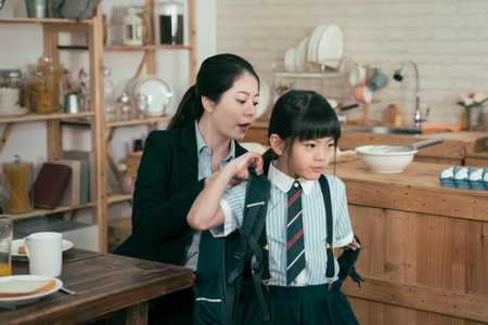 young mother worker in business suit help daughter get ready for school. Mom support child to wear backpack bag in wooden kitchen talking nag to little girl after breakfast time leaving home to study Stockfoto