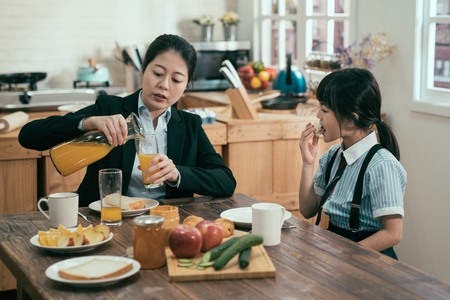 busy single mom in business suit before work in morning prepared handmade healthy meal. young woman mother pour fresh orange juice in glasses for daughter eating breakfast before school. family time.
