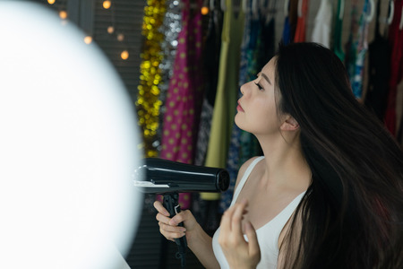side view beautiful japanese girl artist using hair dryer looking at mirror in backstage. woman blowing drying hair with machine sitting at dressing table with clothes hanging on clothing rack Stock Photo