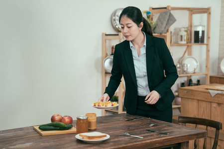 Cooking woman employee in kitchen with wooden table. young elegant wife with love prepared breakfast for husband before work. single asian mom set up healthy meal at home in early morning for child