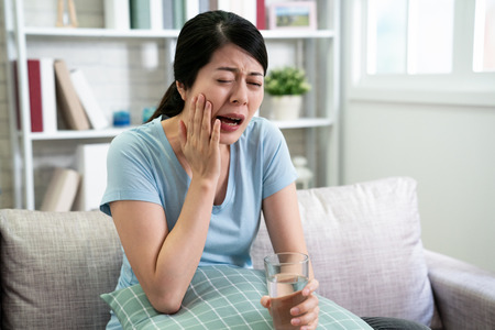 korean asian housewife relaxing on couch having sensitive teeth. young chinese girl holding glass of cold water drinking and tooth hurting pain. illness female suffer toothache at home indoors.