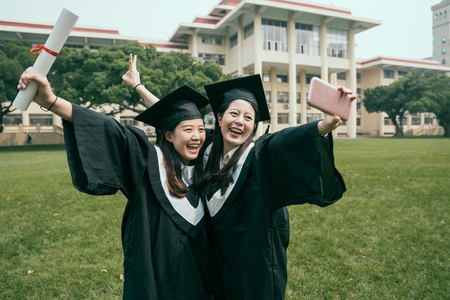 education graduation technology and people concept. group of happy international students in mortar boards and bachelor gowns with diplomas taking selfie by smartphone outdoors on summer sunny day.