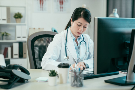attractive concentrated asian female doctor writing prescription on special form. beautiful japanese woman nurse in white coat and stethoscope sitting at desk make note education of medical news.
