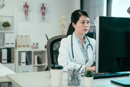 asian female doctor working with personal computer and writing on paperwork. Hospital background. chinese woman medical staff wear white robe in clinic office typing online patient document internet. Banco de Imagens