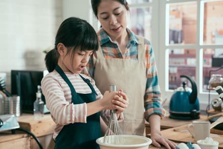 Adorable niño con mamá mezcla harina y huevo en un tazón en casa.