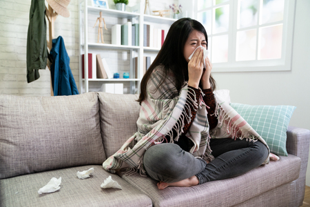 asian illness lady with seasonal infections flu and runny nose using tissue on sofa at home. Imagens - 121830453