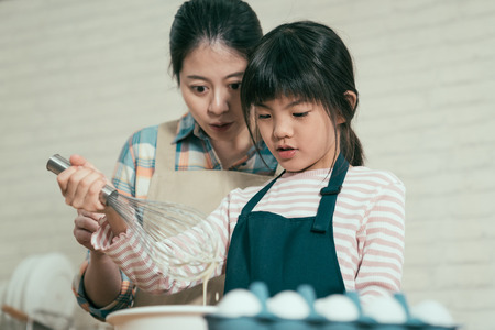 close up elegant asian chinese mom and adorable young chef little girl in apron mixing flour with whisk for baking  easter cake.