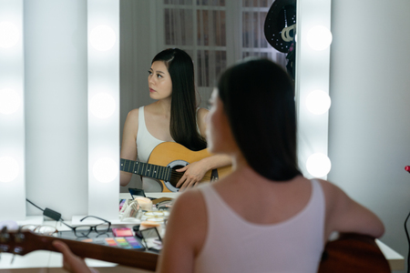 back view of young girl musician sitting at dressing table with mirror and bulbs.