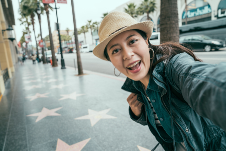 Selfie mania! Excited young asian woman making self portrait standing outdoor on street.