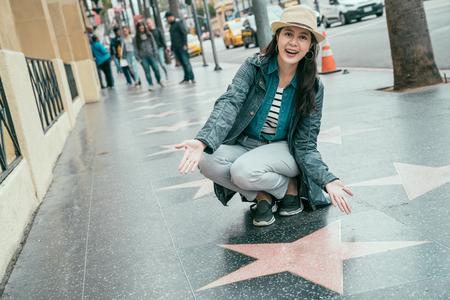 asian woman traveler in hat kneeling down walk of fame star on celebrity boulevard.