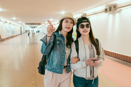 two young asian friends travelers point direction holding mobile phone online map walking in underpass to platform waiting for train. woman sisters travel together commute in union station la.