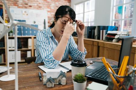 Młoda elegancka kobieta azjatyckiego architekta w okularach zmęczona tarciem nosa i oczu, uczucie zmęczenia i ból głowy. Pojęcie stresu i frustracji przepracowane nad planem budowy budynku zielonej gospodarki. Zdjęcie Seryjne