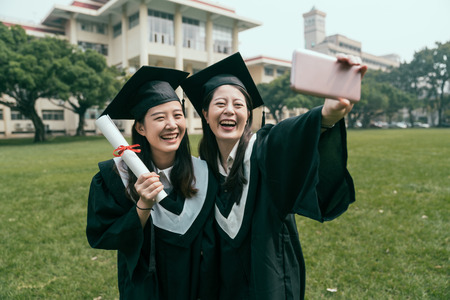 Capturing happy moment. two female college graduates in graduation gowns standing close to each other hold degree taking selfie outdoors. happy girls friends laughing make self portrait by cellphone