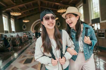 Two beautiful asian girls commute walking in railway train union station talking and laughing. Lifestyle tourism and friendship concepts. young happy women travelers arms in arms historical building