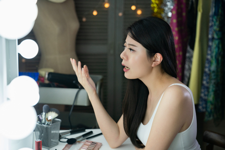 beautiful chinese entertainer in backstage sitting in front of mirror with lights singing practicing with pose hand gesture. young girl musician ready for music competition show in dressing room.