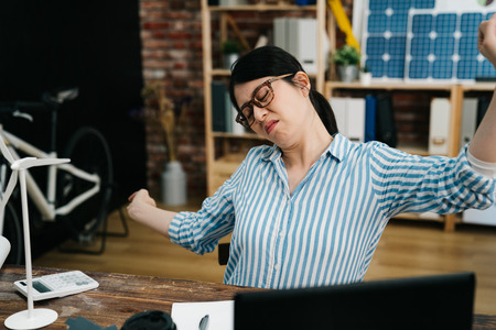 exhausted asian architect woman feeling tired stretching in modern cozy office with frowning face after complete work construction project with windmill model green wind energy eco environment plan