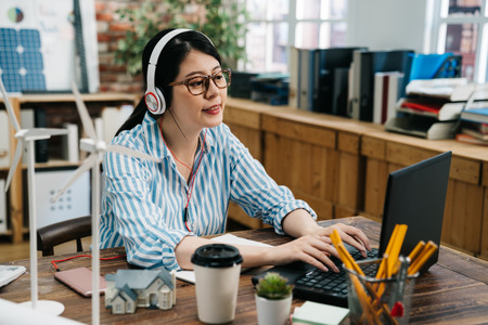 architect asian woman working with laptop and blueprints wearing earphones enjoy melody. engineer inspection in workplace for architectural plan design construction project in headphones listen music