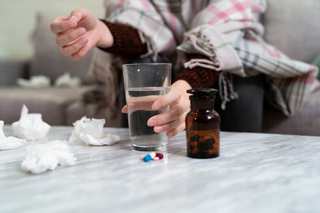 unrecognized women sick resting at home on couch sofa. focus female hand holding water glass with pills tissue napkin handkerchief on table ready to take medicine. Healthcare And Medical concept. Stok Fotoğraf
