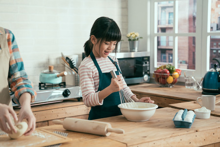 la mamma non riconosciuta passa accanto nella cucina di legno a casa impastando la pasta sul piatto. carina figlia felice che tiene in mano una frusta mescolando farina e uova per cuocere il pane. bambino che fa sorpreso per la festa della mamma.