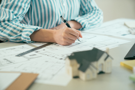 unrecognized asian young woman working on plan project at site construction work in office. female hand holding pen drawing design building on blueprint sitting at desk. blurred view 3d house model.