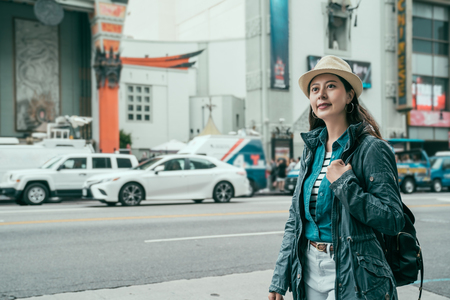 Asian woman travel backpacker vivacious tourism in los angeles standing on hollywood walk of fame with beautiful beaming smile on busy street. Chinese theatre old monument in background in urban.
