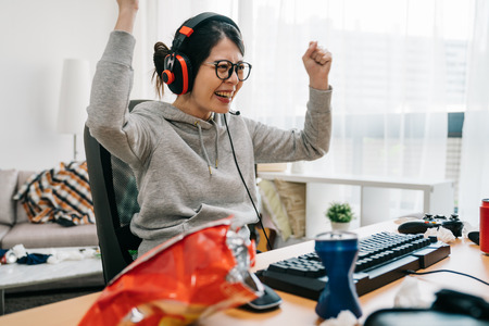 Professional gamer girl putting on headset and starts playing online video game on personal computer. Casual asian geek woman. happy female in eyeglasses winning pc game at home with yes hand gesture