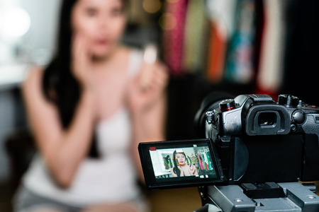 blurred image attractive chinese female celebrity recording video tutorial while applying makeup looking at camera fixed on tripod in dressing room. asian model introduce cosmetic product backstage