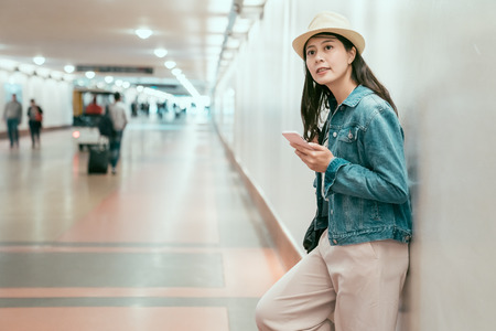 joyful asian local girlfriend leaning on wall in passageway waiting for boyfriend having date. smiling young woman traveler browsing online website relaxing in underpass looking around union station