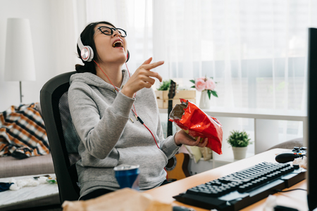 asian weird computer geek stay at home on summer vacation. high school girl laughing watching online series comedy movie on pc cheerful eating junk food snack chips cookies unhealthy lifestyle. 版權商用圖片